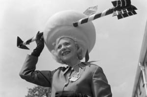 1968 Gertrude Shilling wearing an outrageous Wide Brimmed Hat with arrow going through it at Ascot races